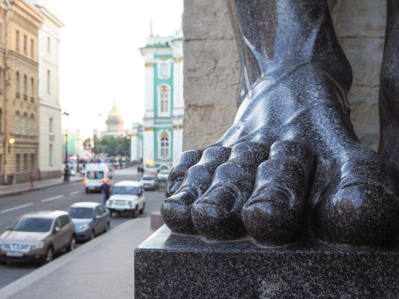 De voet van het monument op de achtergrond van Paleisvierkant in Heilige Petersburg Het close-up van voetatlanta stock afbeelding