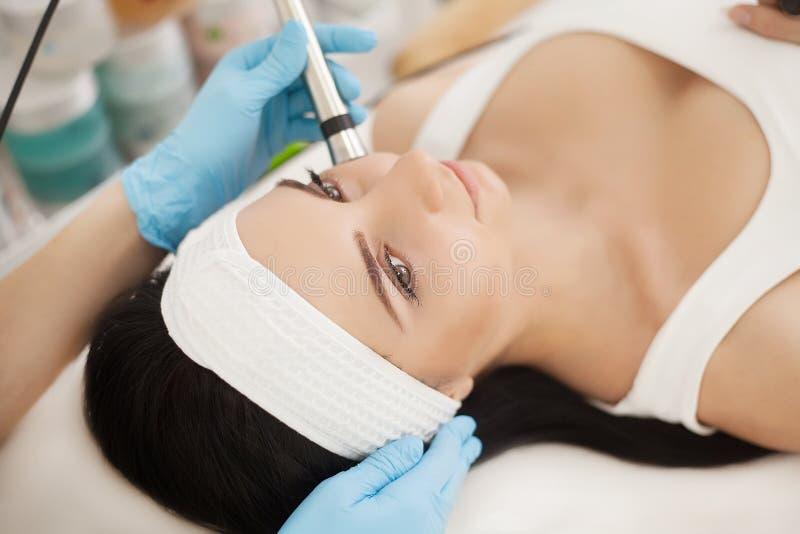 De voet van de vrouw in het water Vrouw die de analyse van de gezichtshuid ontvangen cosmetology stock foto