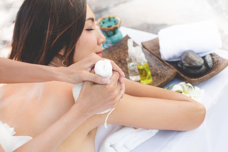 De voet van de vrouw in het water Jonge Aziatische Vrouw die massage met hete kruidenballen voor diepe ontspanning hebben stock foto's