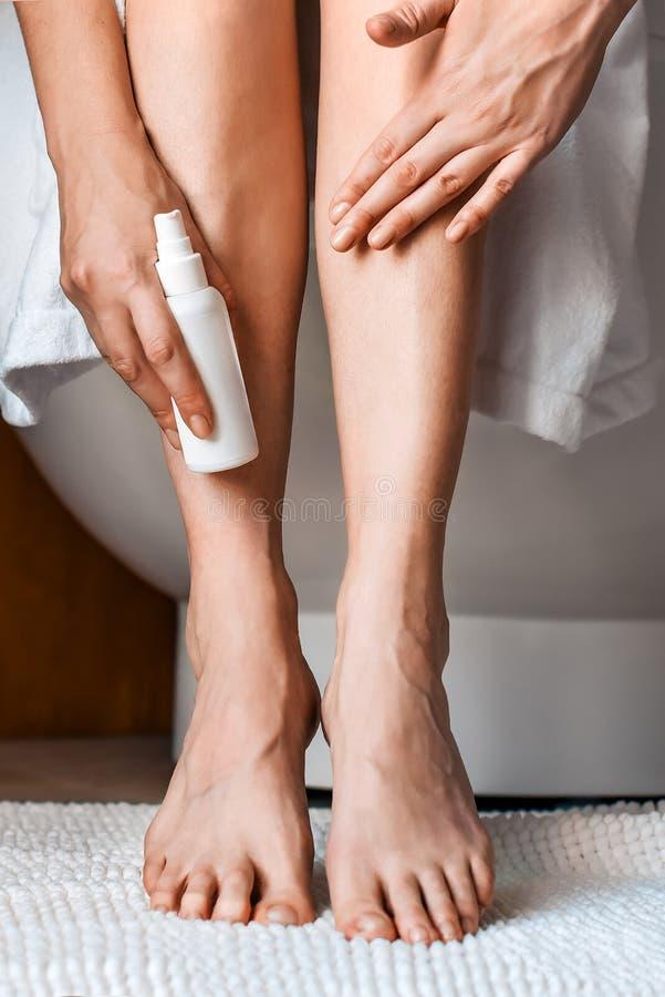 De voet van de vrouw in het water Jonge vrouw in de badkamers, die haar benen strijken Anti-anti-cellulitebehandeling voor mooie  royalty-vrije stock afbeelding
