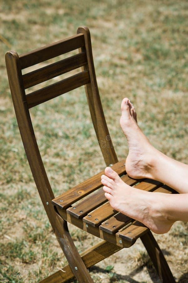 De voet van de vrouw op houten stoel openlucht stock foto's
