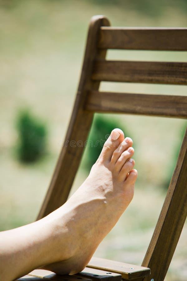 De voet van de vrouw op houten stoel openlucht royalty-vrije stock foto's