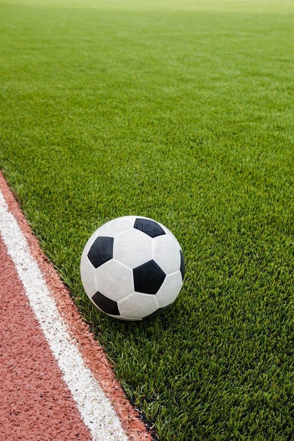 De voetbal is op het kunstmatige gebied van het grasvoetbal stock foto