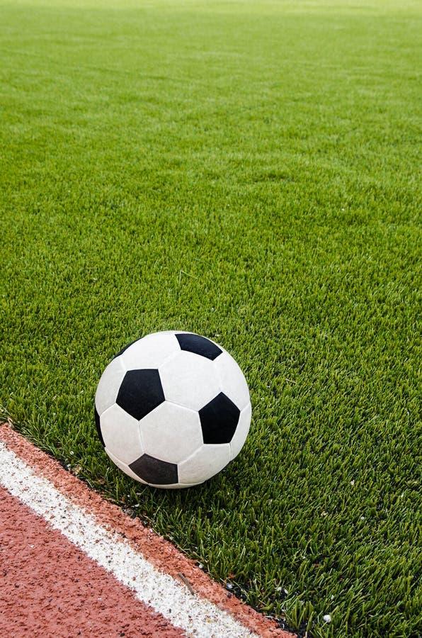 De voetbal is op het kunstmatige gebied van het grasvoetbal in het stadion royalty-vrije stock fotografie