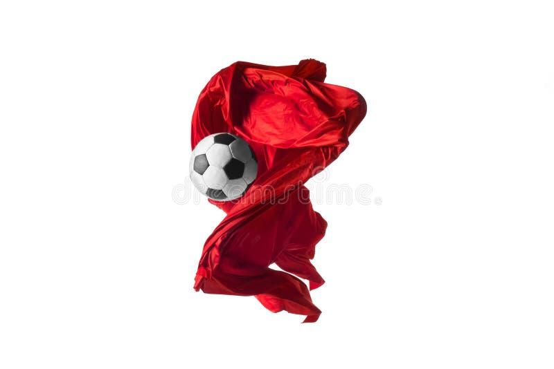 De voetbalbal en de Vlotte elegante transparante rode doek isoleerden of scheidden op witte studioachtergrond stock afbeelding