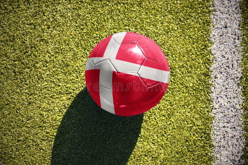 De voetbalbal met de nationale vlag van Denemarken ligt op het gebied stock foto