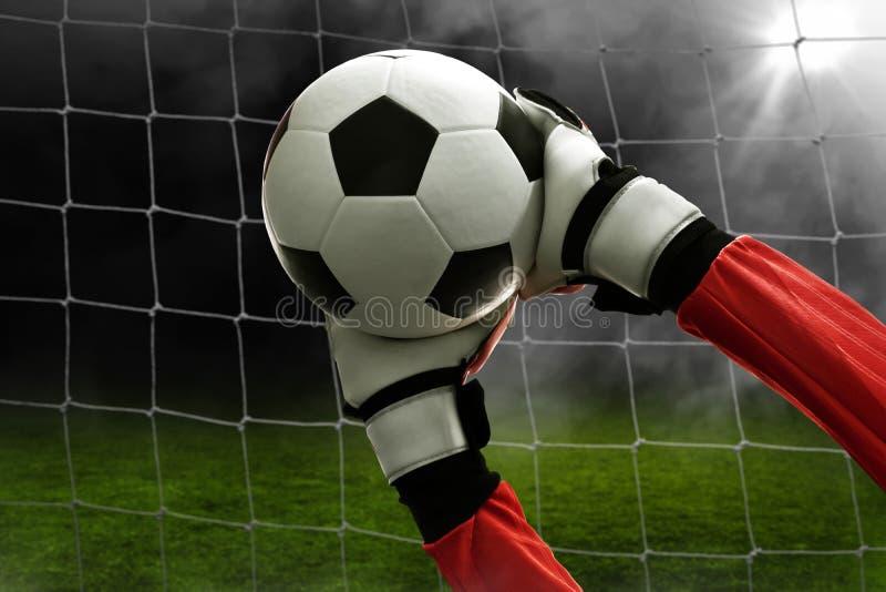 De voetbalkeeper vangt de bal stock foto's