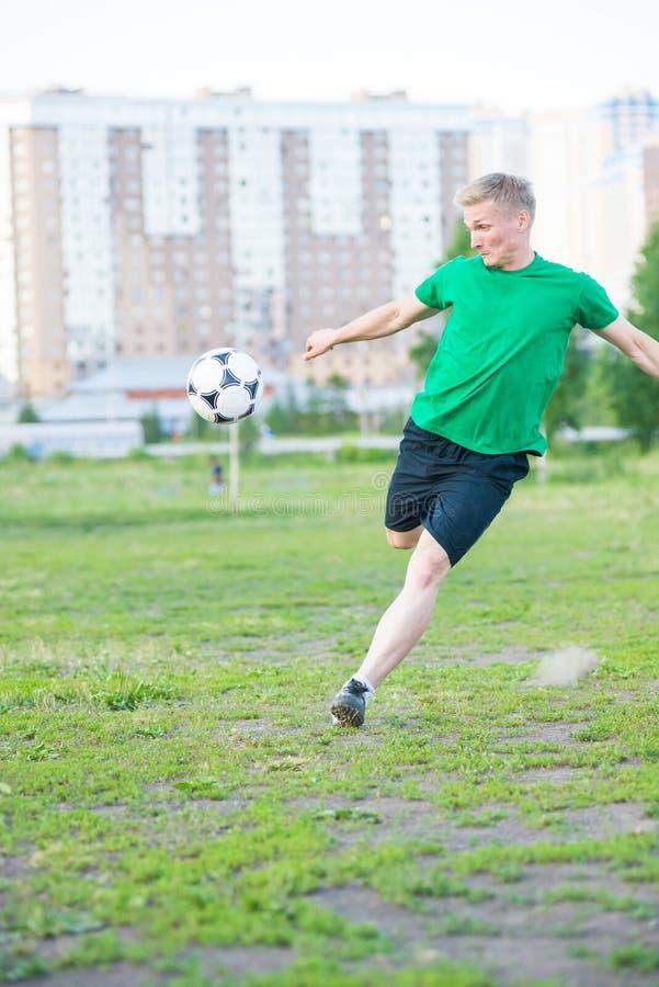 De voetballer raakt sterk de bal stock fotografie