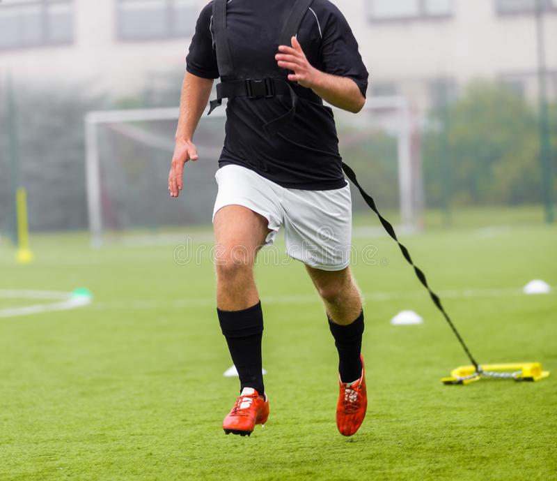De voetbalster loopt terwijl het slepen van gewichten achter hem Het lopen met gewichtenvoetbal opleiding royalty-vrije stock afbeeldingen