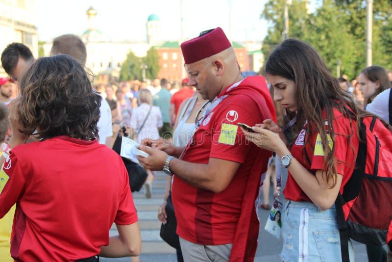De voetbalventilators op de straten van Moskou gaan online van hun smartphones en horloge online informatie royalty-vrije stock foto