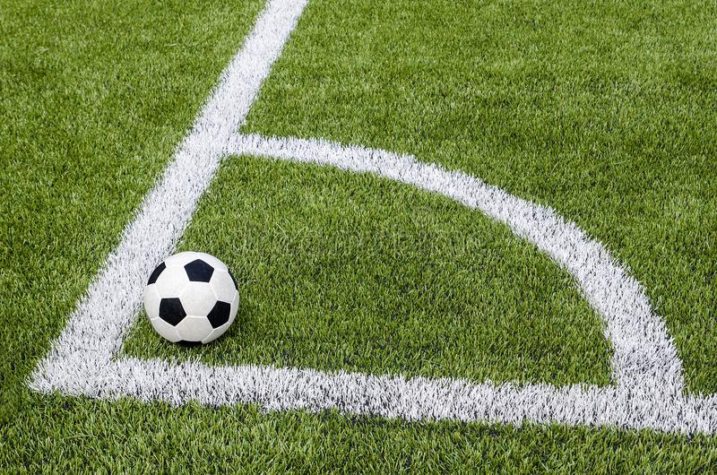 De voetbalvoetbal in de hoek op het kunstmatige groene grasgebied royalty-vrije stock foto's