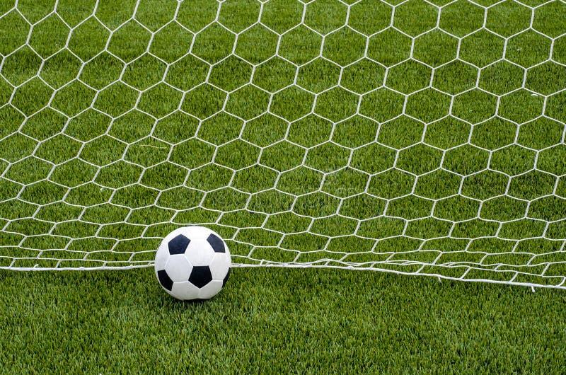 De voetbalvoetbal met het net op het kunstmatige groene gebied van het grasvoetbal stock afbeelding