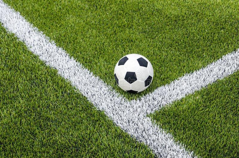 De voetbalvoetbal op de witte lijn op het kunstmatige groene grasgebied royalty-vrije stock foto