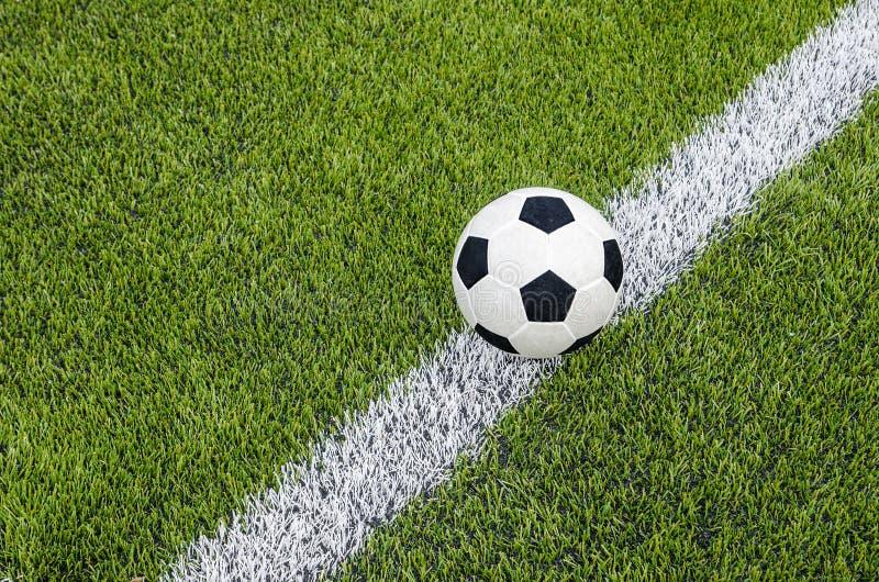 De voetbalvoetbal op de witte lijn op het kunstmatige groene grasgebied stock foto