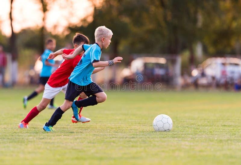 De voetbalwedstrijd van jonge kinderenspelers op voetbalgebied stock afbeeldingen