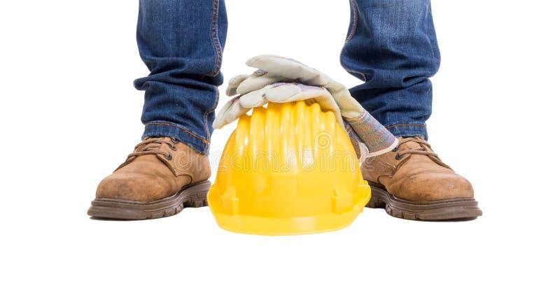 De voeten, de helm en de handschoenen van de bouwbouwer royalty-vrije stock fotografie