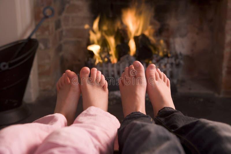 De voeten die van het paar bij een open haard verwarmen royalty-vrije stock afbeeldingen