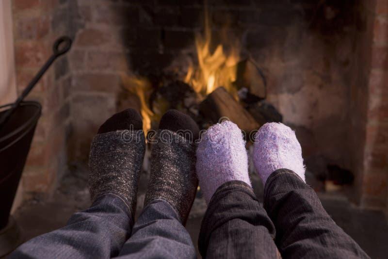 De voeten die van het paar bij een open haard verwarmen stock fotografie