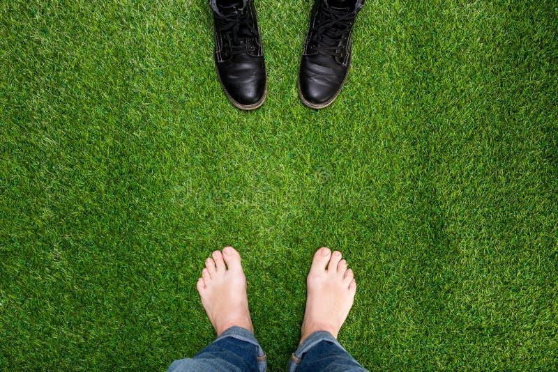 De voeten die van mensen op groen gras rusten die zich tegenover laarzen bevinden stock foto