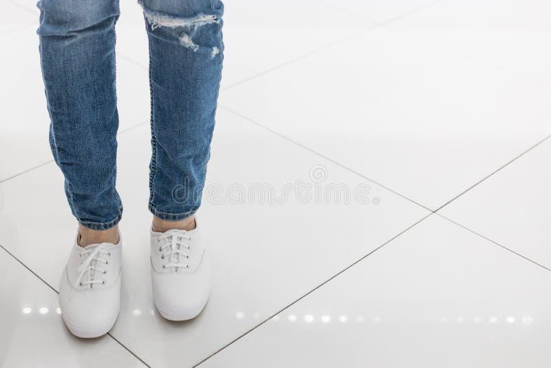 De voeten in jeans en witte tennisschoenen bevinden zich op de vloer van witte tegels in de schoenopslag royalty-vrije stock foto