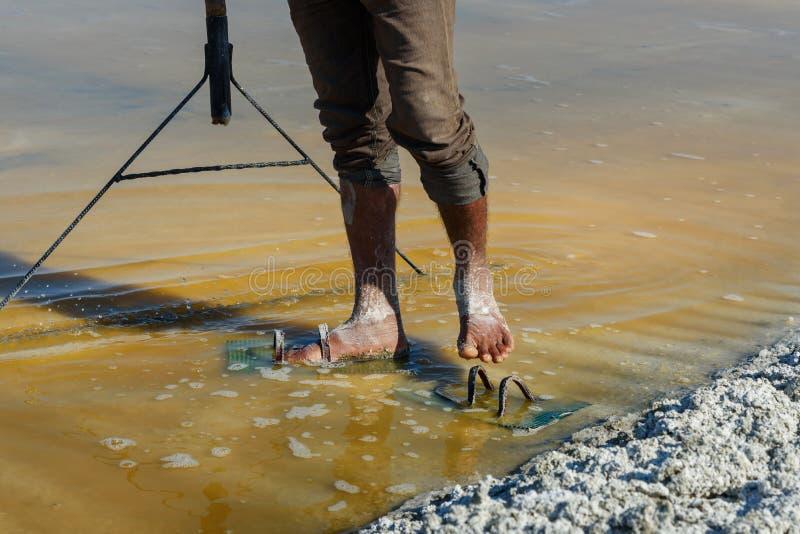 De voeten van de arbeider door zout op zout landbouwbedrijf op Sambhar Salt Lake worden behandeld dat Rajasthan India royalty-vrije stock foto