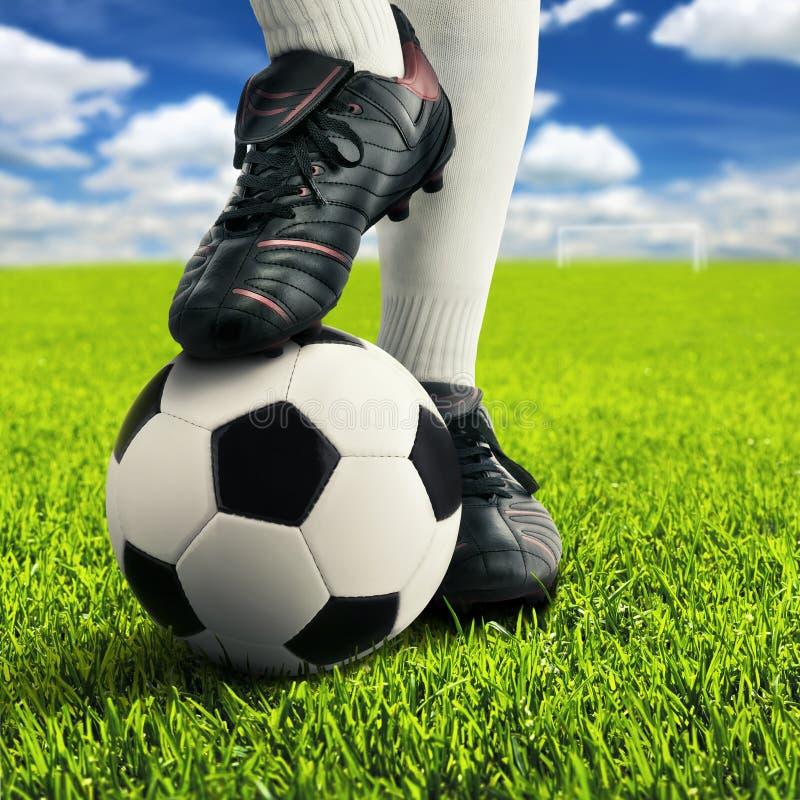 De voeten van de voetballer in toevallig stellen stock fotografie