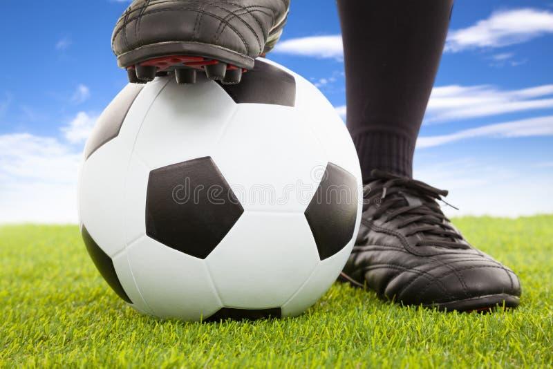 De voeten van de voetballer in toevallig stellen op een open speelgebied stock foto's