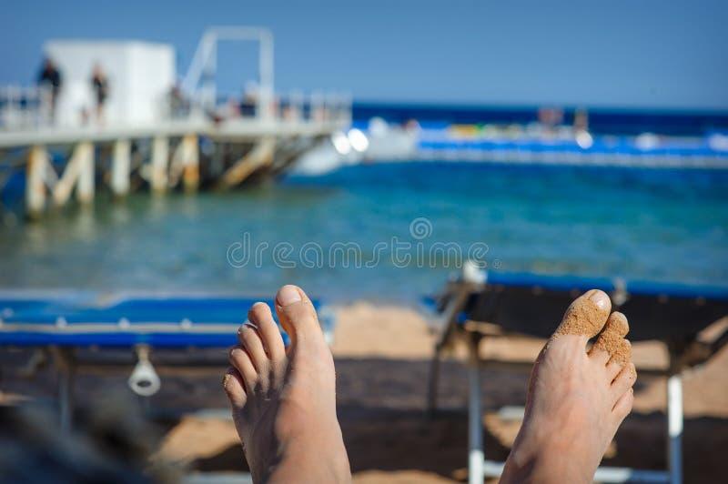De voeten van de vrouw in het zand op overzeese achtergrond royalty-vrije stock afbeeldingen