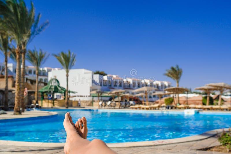 De voeten van de vrouw tegen zwembad bij het rusten stock afbeelding