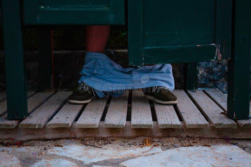 De voeten van een mens die in het toilet zit Openbare houten WC met houten raad op de bodem Het concept van Stomackproblemen royalty-vrije stock afbeeldingen