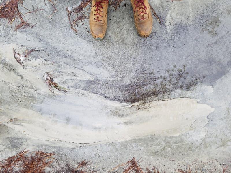De voeten van de persoon in bruine leerschoenen die zich op een doorstane concrete grond bevinden stock afbeelding