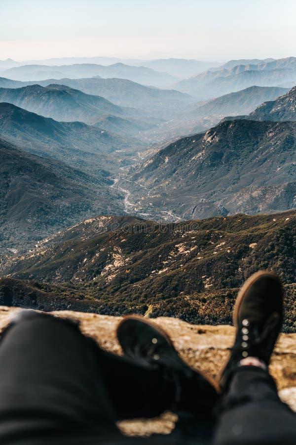 De voeten van de persoon op een gebied met een verbazende mooie mening van bergen en heuvels in de afstand royalty-vrije stock fotografie