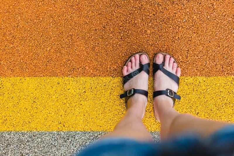 De voeten van vrouwen in pantoffels die zich bij de lijnen bevinden Persoonlijk perspectief van persoon die zijn voeten bekijken stock foto's