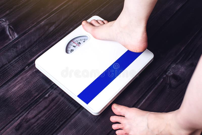 De voeten van vrouwen zijn op mechanische schalen voor gewichtscontrole royalty-vrije stock foto