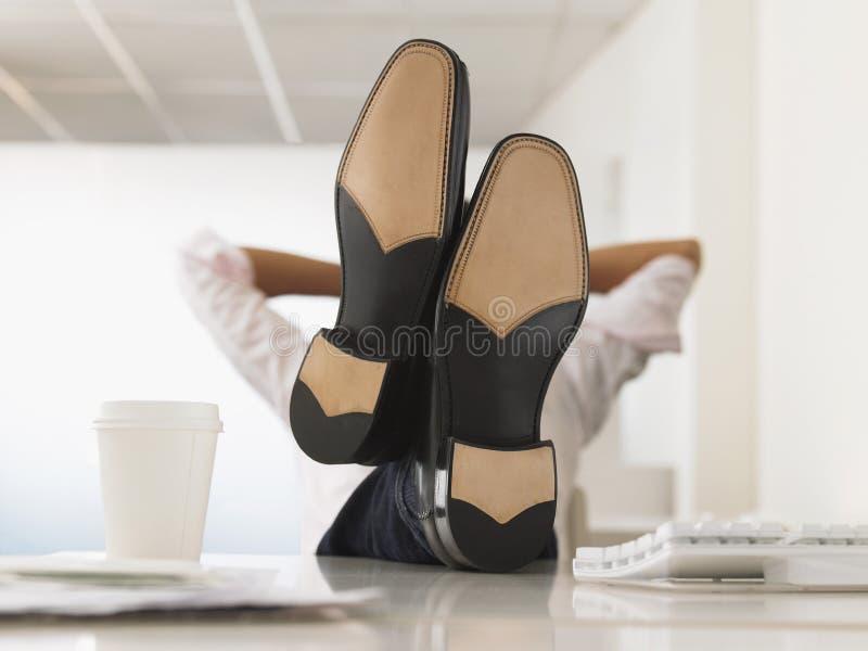 De Voeten van zakenmanreclining with his omhoog op Bureau stock foto's