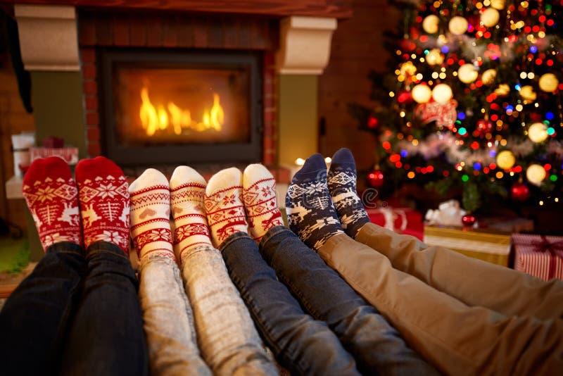 De voeten in wol mept dichtbij open haard in Kerstmistijd stock afbeeldingen