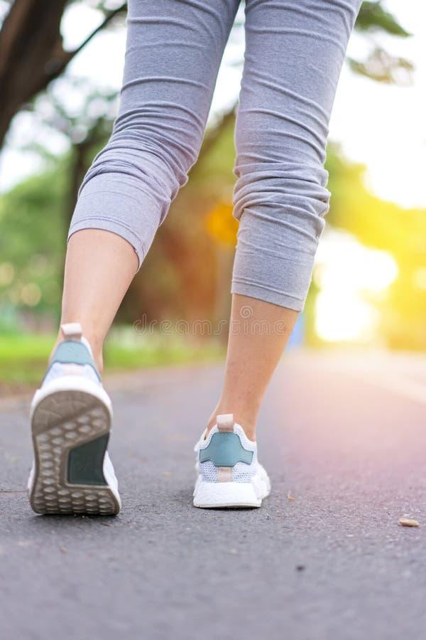 De voetenvrouw die van de atletenagent in groen park langs weg bij zonsopgangochtend loopt stock foto's