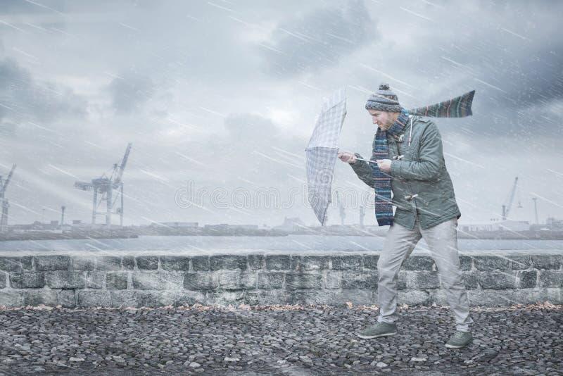 De voetganger met een paraplu ziet sterke wind en regen onder ogen stock afbeelding