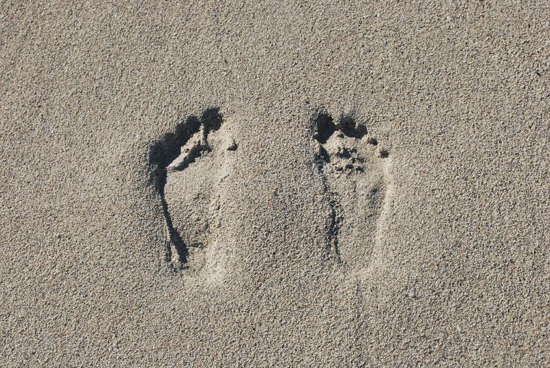Twee voetafdrukken in het zand