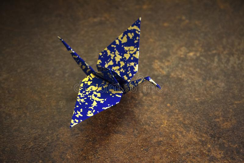 De vogel van de origami Kraan, zwaan gemaakt die van Japans document wordt gemaakt Blauwe Indigo en gouden kleuren van origami op stock foto