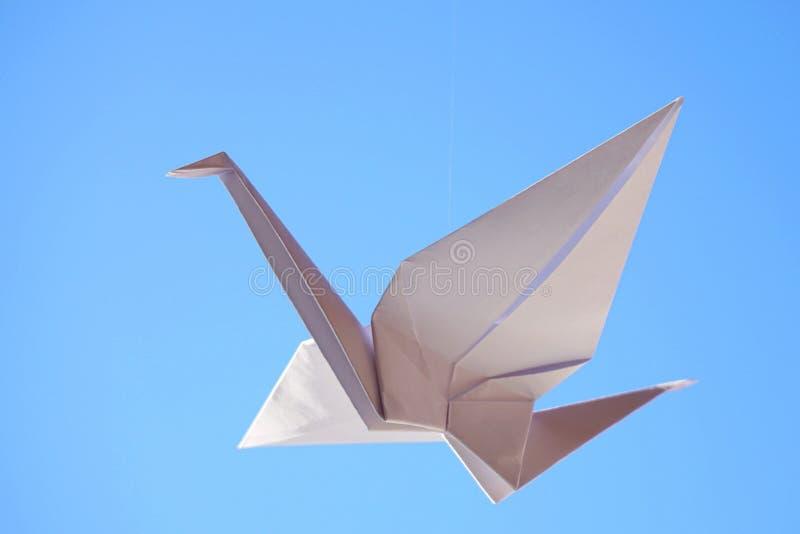 De vogel van de origami Vliegende origamivogel op blauwe achtergrond royalty-vrije stock foto's