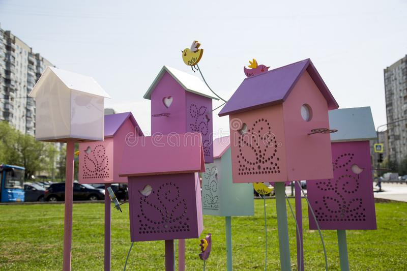 De vogelhuizen zijn gekleurd op de achtergrond van huizen en blauwe hemel royalty-vrije stock fotografie