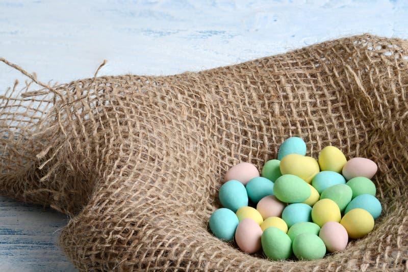 De vogelnest van de close-upjute met Pasen-suikergoedeieren stock foto