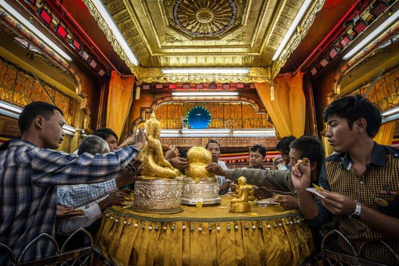 De volkeren maken verdienste door het bladgoud in de Pagode van Phaung Daw Oo bij Inle-Meer, Myanmar te plakken royalty-vrije stock afbeelding