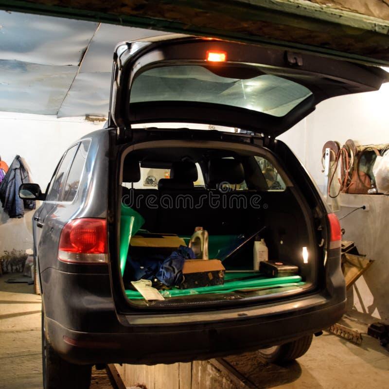 De Volkswagen-auto is in de garage met een open boomstam stock afbeeldingen