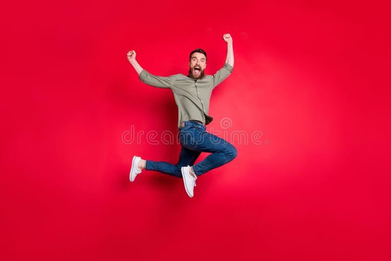 De volledige foto van het lengtelichaam van de gedraaide verheugende mens die met geluk springen die zijn team het winnen zien be stock afbeelding