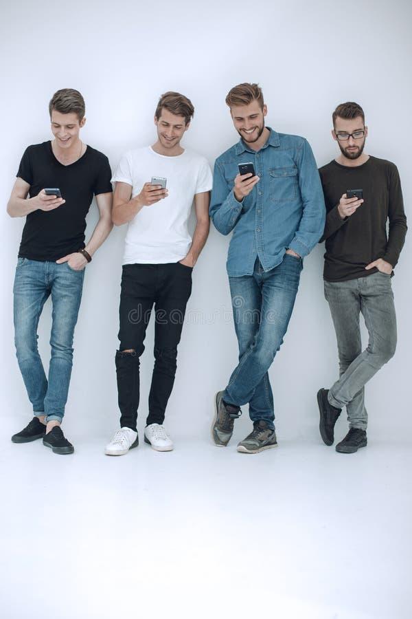 In de volledige groei Groep vrienden met smartphones stock fotografie