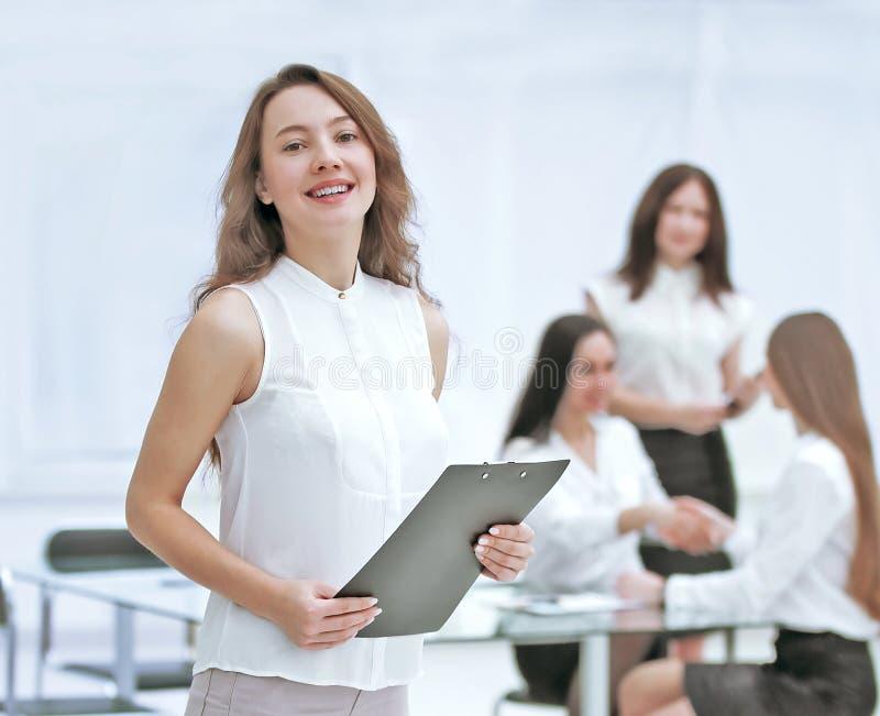 In de volledige groei succesvolle bedrijfsvrouw met klembord op de achtergrond van commercieel team royalty-vrije stock foto's