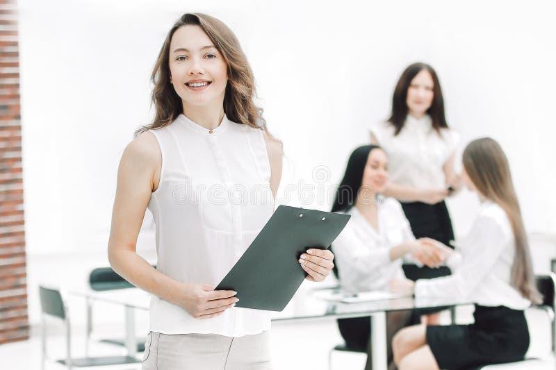 In de volledige groei succesvolle bedrijfsvrouw met klembord op de achtergrond van commercieel team stock foto