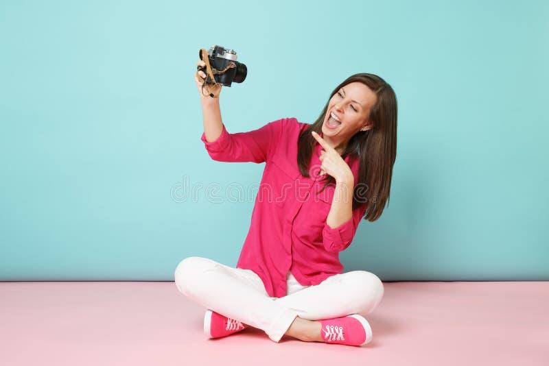 De volledige jonge vrouw van het lengteportret in het roze witte de broek van de overhemdsblouse zitten op de camera van de vloer stock afbeeldingen